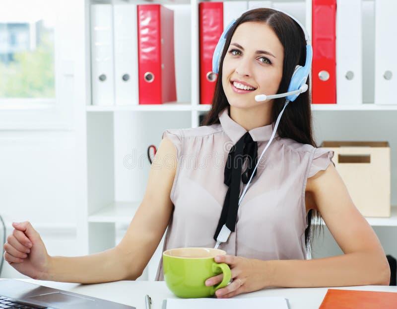 有公务便装成套装备的年轻友好的拉丁妇女使用耳机 图库摄影