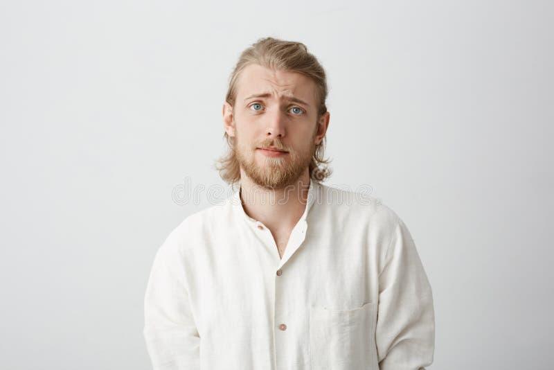 有公平的头发举的眼眉的英俊的有胡子的白种人人,看非常逗人喜爱和阴沉,好象请求帮忙或 免版税图库摄影
