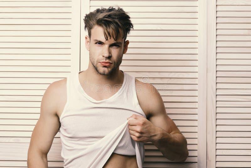 有公平的头发的人在轻的木板条背景 有诱人的面孔的强壮男子投入显示吸收的T恤杉 图库摄影