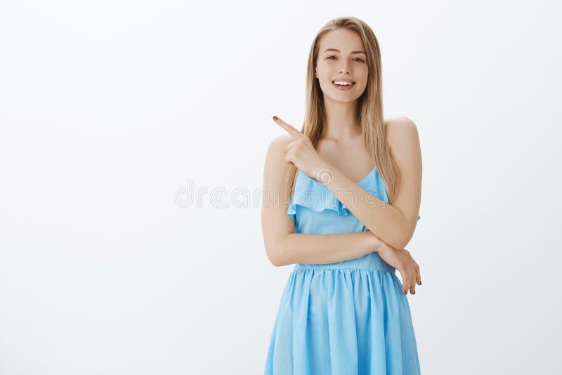 有公平的头发的时髦和确信的漂亮的女人在典雅的蓝色礼服问问题作为seing的有趣 库存图片