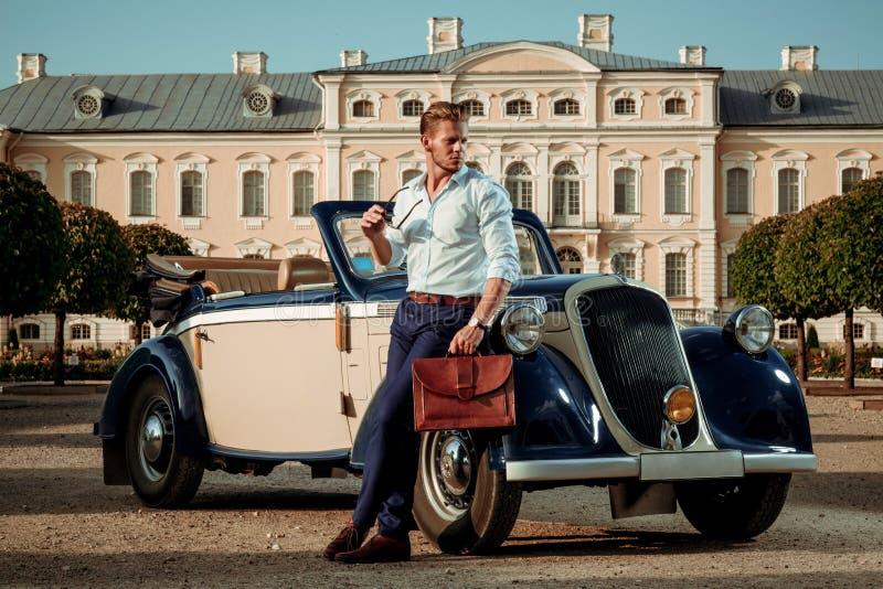 有公文包的确信的富裕的年轻人在经典敞篷车附近 库存照片