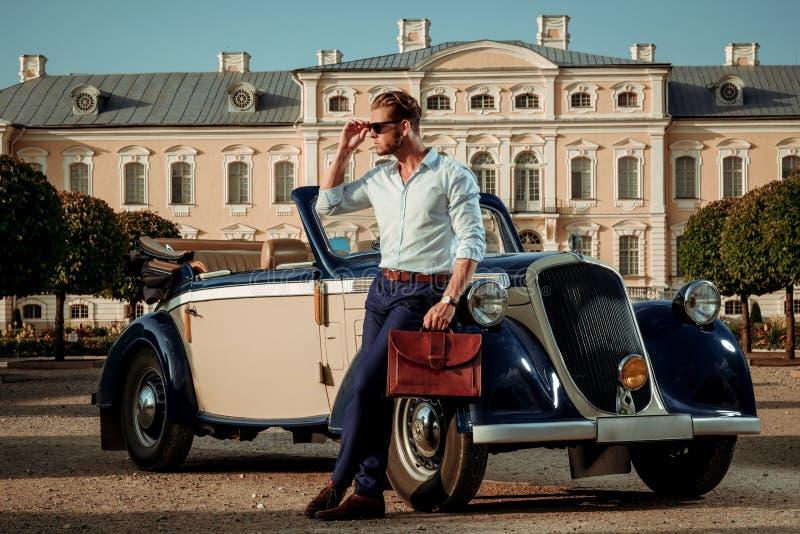 有公文包的确信的富裕的年轻人在经典敞篷车附近 库存图片