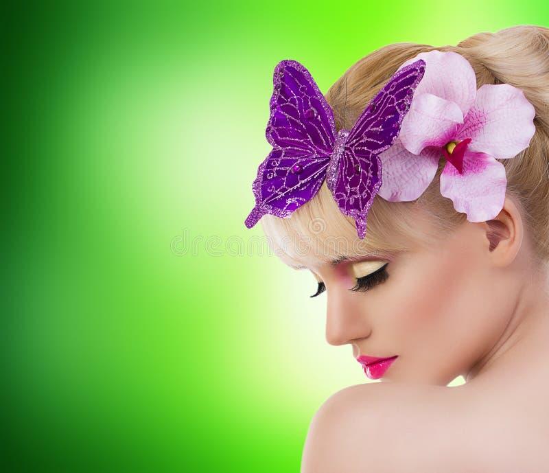 有兰花花和蝴蝶的美丽的白肤金发的女孩 免版税库存图片