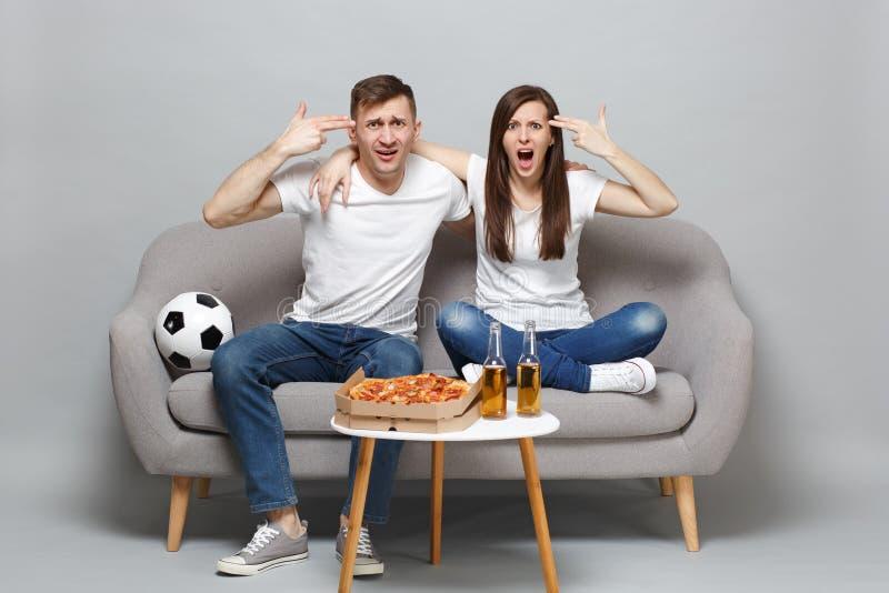 有关夫妇妇女人足球迷使支持喜爱的队,对头的点手指振作,好象他射击 库存照片