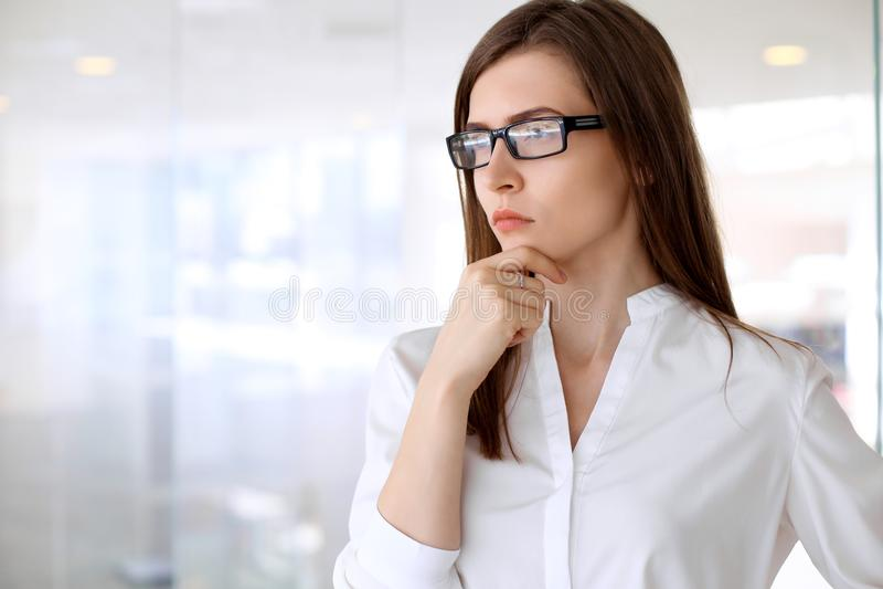 有关的现代女商人看起来,当站立在办公室时 库存照片