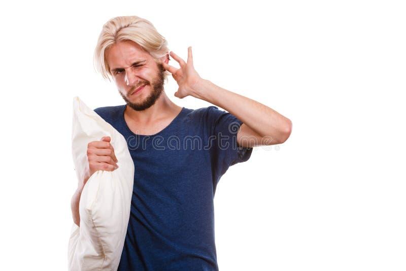 有关闭他的耳朵的枕头的困人 库存照片