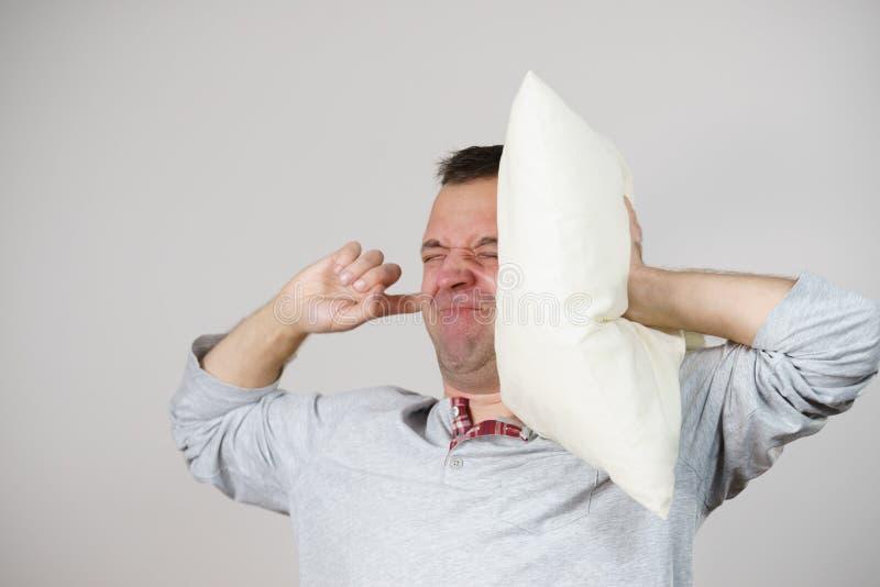 有关闭他的耳朵的枕头的困人 库存图片