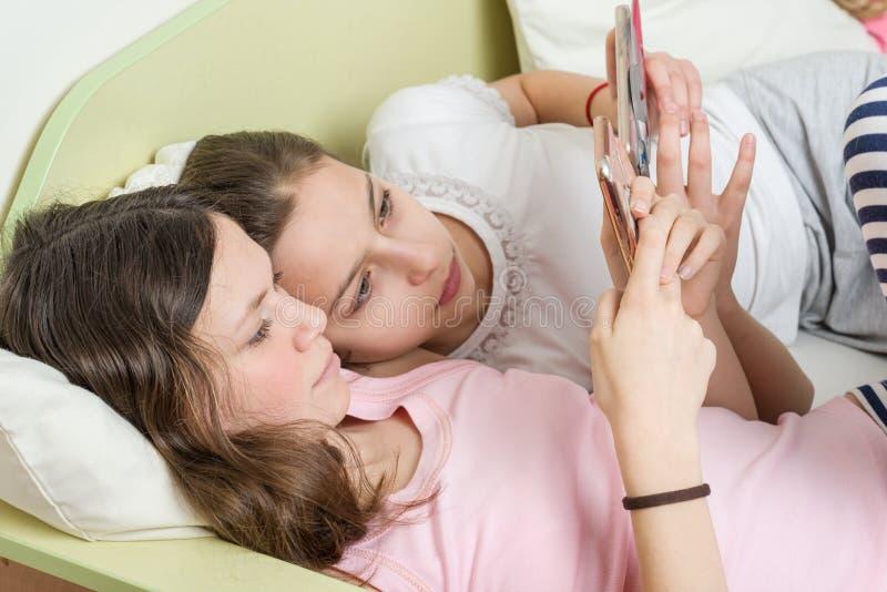 有兴趣的女孩少年观看他们在他们的智能手机的喜爱的青少年的电视系列节目 谎言在床上在家在他的屋子里 库存照片