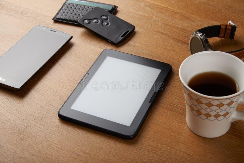 有其他对象的E书设备在桌上 免版税图库摄影