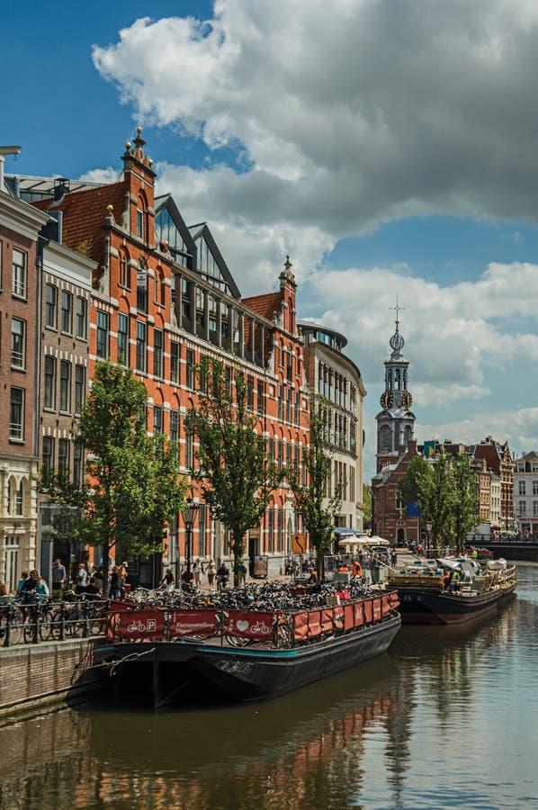 有典型的房子的宽运河,尖顶,在阿姆斯特丹停泊了小船和蓝天 免版税库存照片