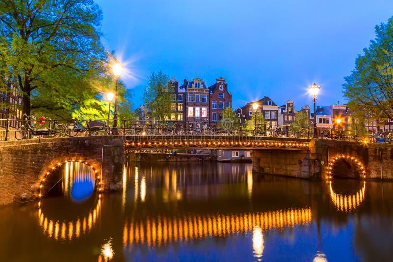 有典型的荷兰房子的阿姆斯特丹运河和有启发性桥梁在暮色蓝色小时在荷兰,荷兰 美丽如画  库存照片