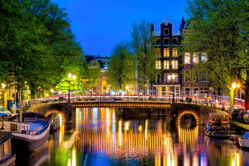 有典型的荷兰房子的阿姆斯特丹运河和桥梁在暮色蓝色小时在荷兰,荷兰 库存图片