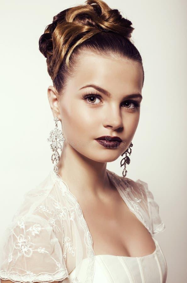 有典雅的发型的年轻新娘,在豪华婚礼礼服 免版税库存图片