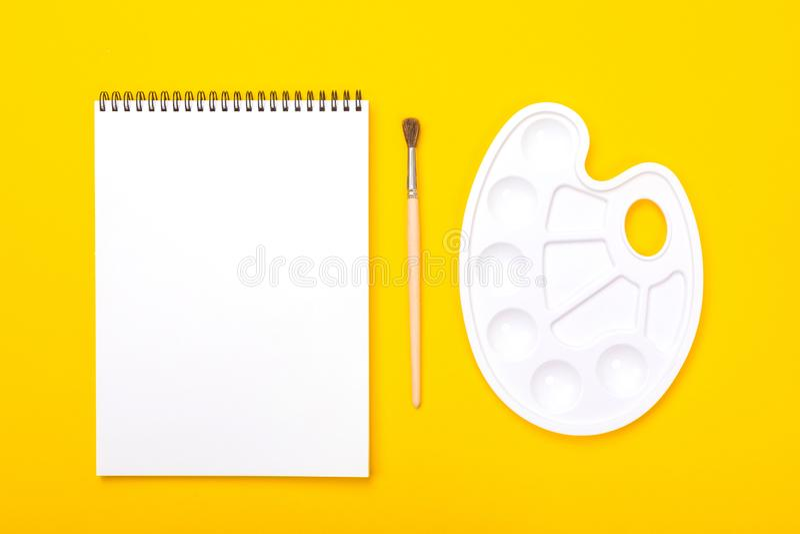 有册页的造型艺术在橙色背景的调色板绘的和刷子 免版税库存图片