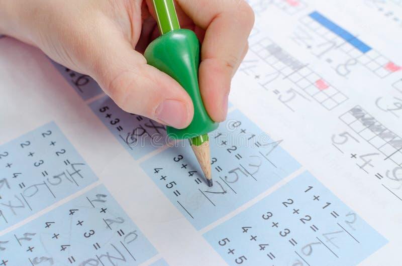有写的工具儿童的手为由铅笔,homewortk,算术不正确藏品的帮助  免版税图库摄影