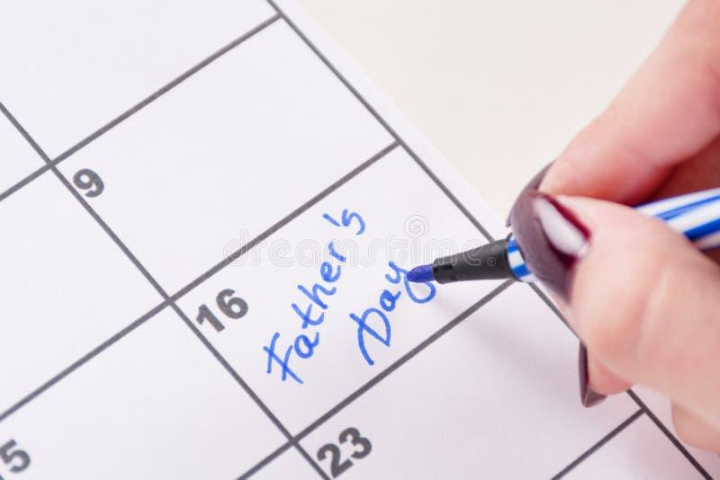 有写词父亲节的蓝色感觉的笔的女孩手在日历 免版税库存图片