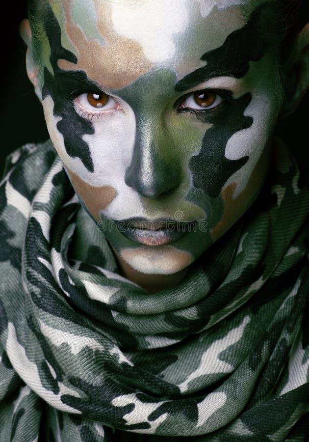 有军用样式衣物的美丽的年轻时尚妇女和面孔绘构成 库存照片