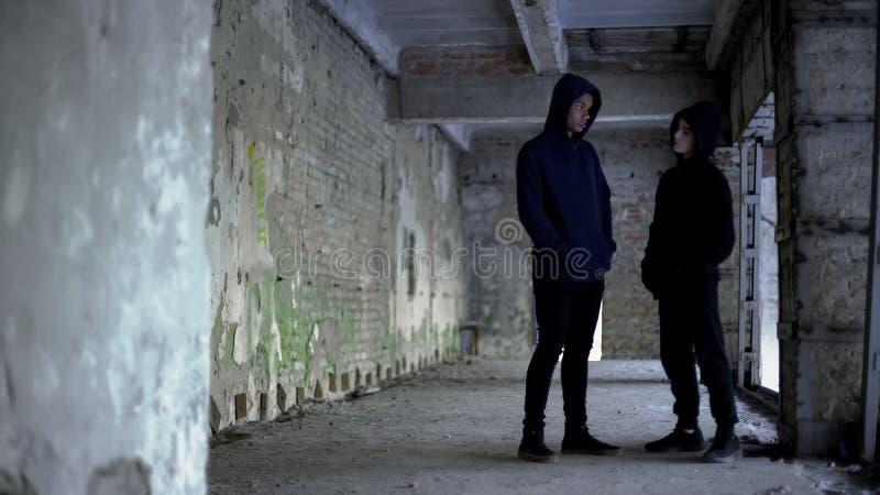 有冠乌鸦的男孩谈话在被破坏的大厦,少年帮会,年轻罪犯 免版税图库摄影