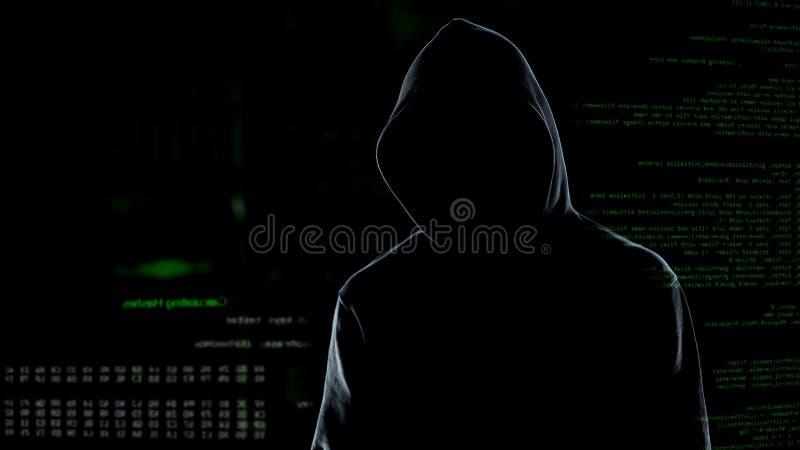 有冠乌鸦身分的匿名的男性黑客在生气蓬勃的计算机编码前面 库存照片