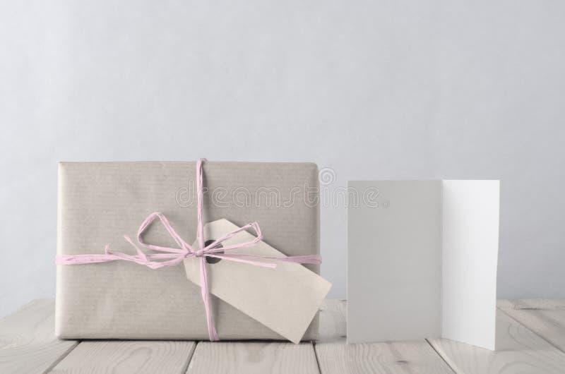 有冰冷的桃红色酒椰和贺卡的被包裹的礼物盒 库存图片