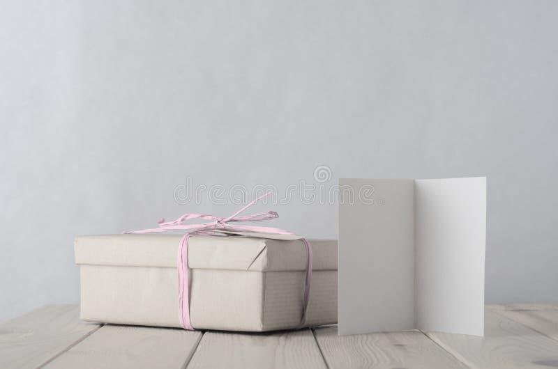 有冰冷的桃红色酒椰蝶形领结和Greetin的被包裹的礼物盒 库存照片