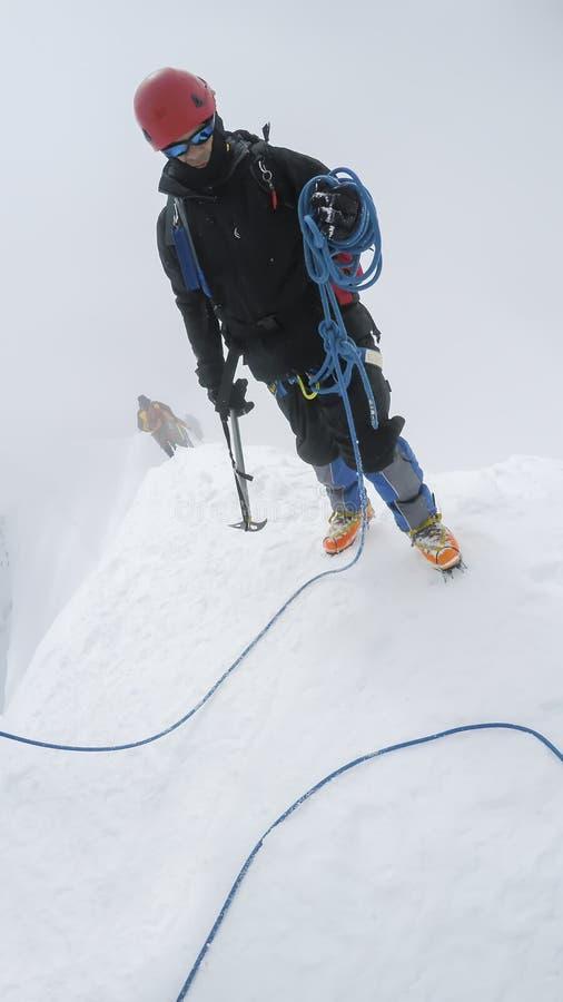 有冰斧的登山家在一个晴朗的冬日到达一座多雪的山的上面 免版税库存照片