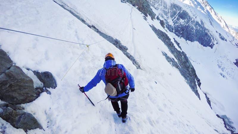 有冰斧的登山家在一个晴朗的冬日到达一座多雪的山的上面 图库摄影