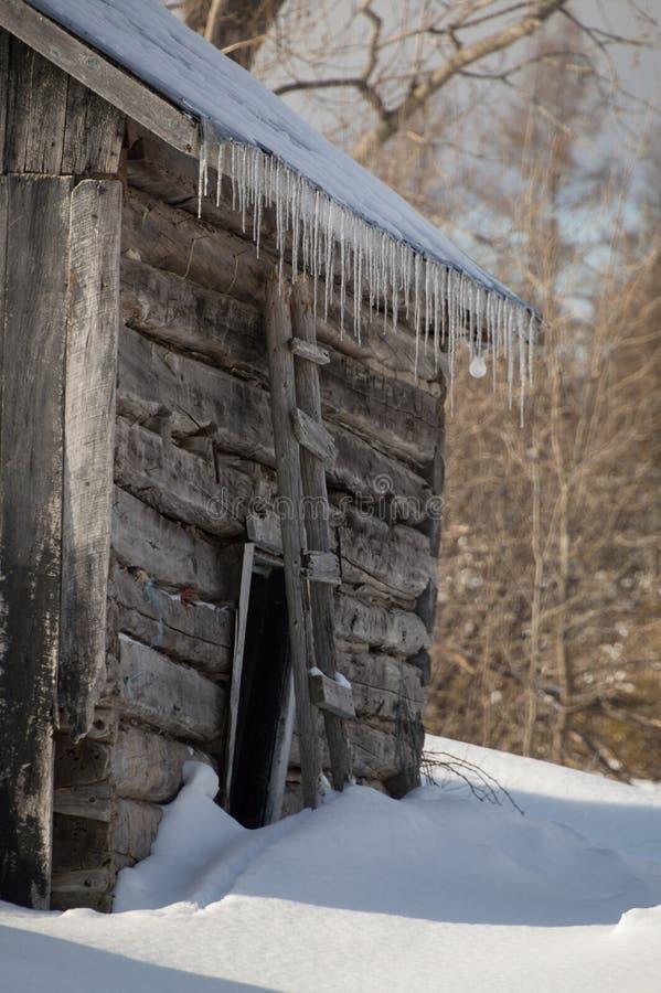 有冰柱的斯诺伊老原木小屋谷仓 免版税库存图片