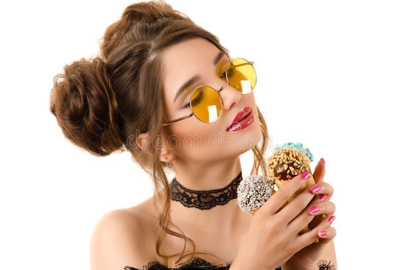 有冰淇凌的美丽的端庄的妇女在手上 库存照片