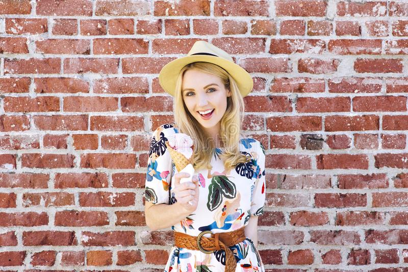 有冰淇淋锥体的千福年的白肤金发的妇女站立对一个砖墙在一个夏日 免版税库存照片