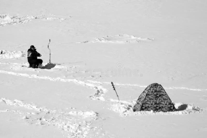 有冰螺丝的冬天渔夫在冻湖做冰孔 图库摄影