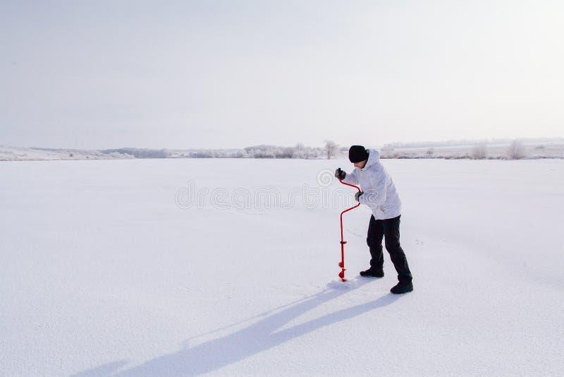 有冰螺丝的冬天渔夫在冻湖 免版税库存照片