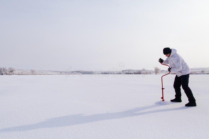 有冰螺丝的冬天渔夫在冻湖 库存图片