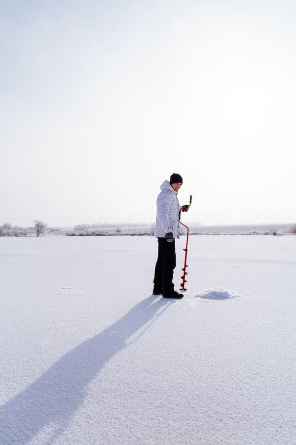有冰螺丝的冬天渔夫在冻湖 库存照片