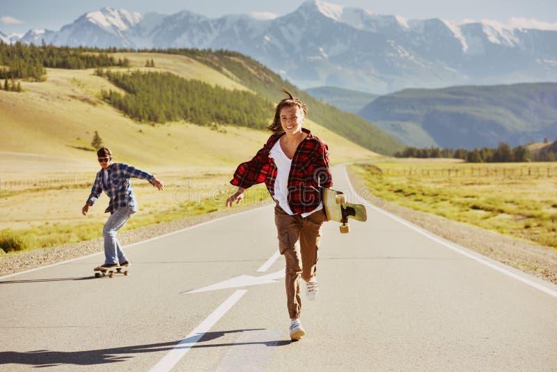 有冰鞋和longboards的愉快的朋友获得乐趣 库存图片