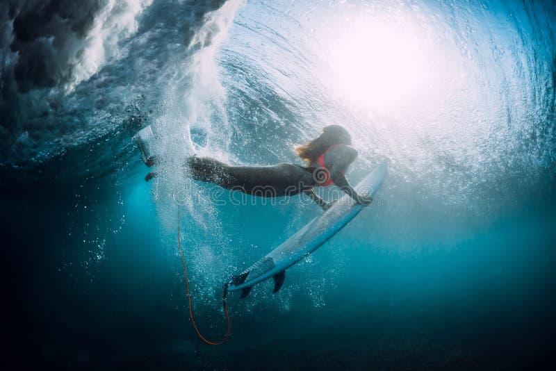有冲浪板下潜的冲浪者女孩水下与下面桶海浪 免版税库存图片