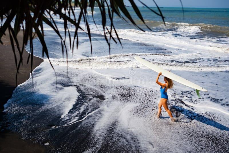 有冲浪板步行的少妇在黑沙子海滩 库存照片
