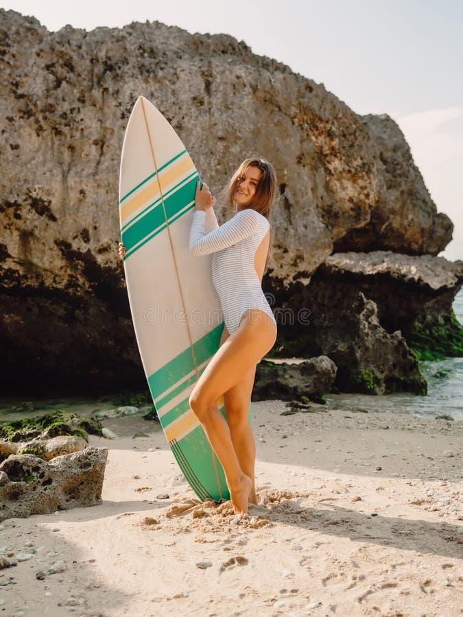 有冲浪板的可爱的海浪女孩保持平衡在海滩的 站立在海滩的冲浪者妇女 图库摄影