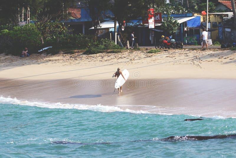 有冲浪板的女孩在海滩 库存照片