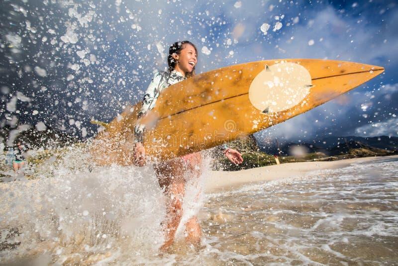 有冲浪板的女孩在飞溅波浪在海滩 库存照片