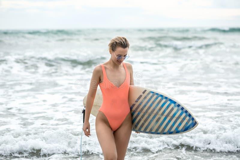 有冲浪板的妇女在海滩 免版税库存图片