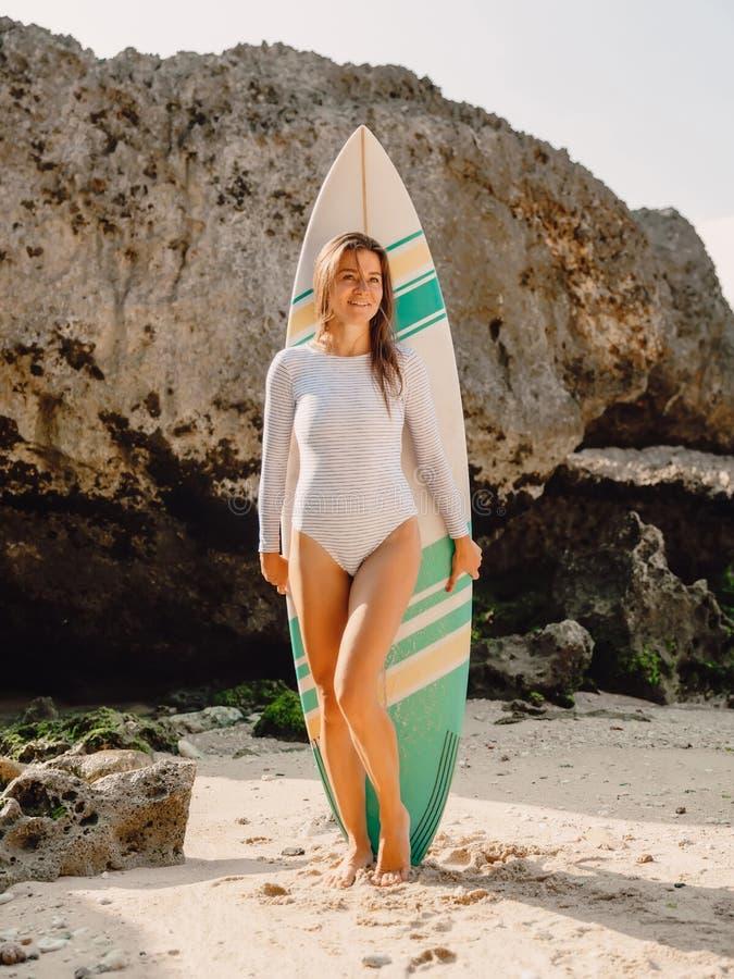 有冲浪板的年轻冲浪者女孩保持平衡在海滩的 站立在海滩的冲浪者妇女 免版税库存照片