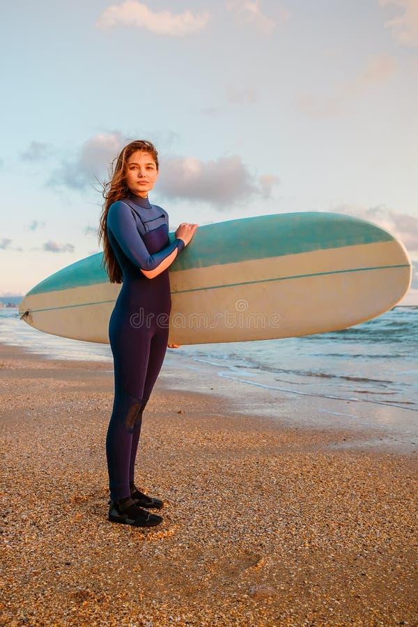 有冲浪板的年轻冲浪者妇女在温暖的日落或日出的一个海滩 库存照片