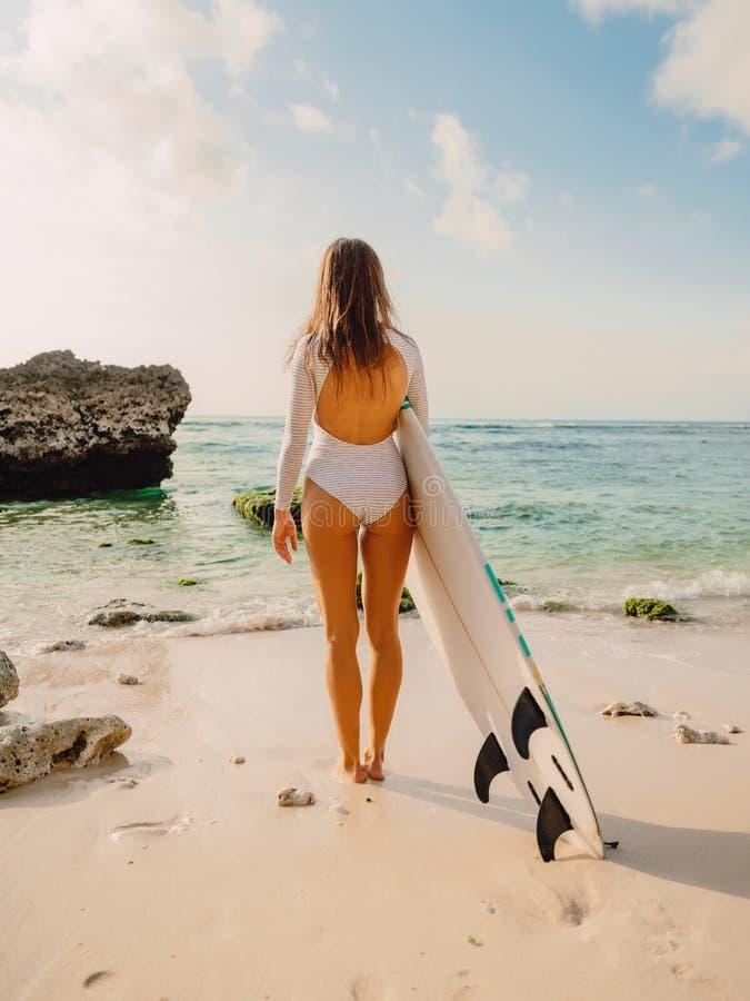 有冲浪板的年轻海浪女孩观看在海洋的 站立在海滩的冲浪者妇女 库存照片