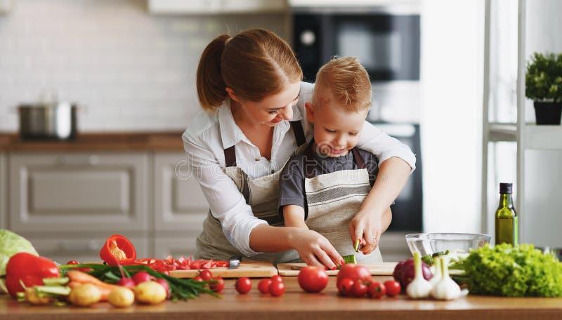 有准备菜沙拉的儿童儿子的幸福家庭母亲 免版税库存图片