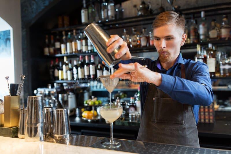 有准备鸡尾酒的振动器的男服务员在酒吧 库存照片