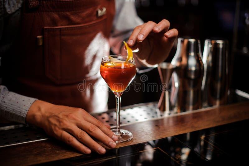 有准备鸡尾酒的玻璃和柠檬皮的侍酒者在酒吧 免版税库存图片