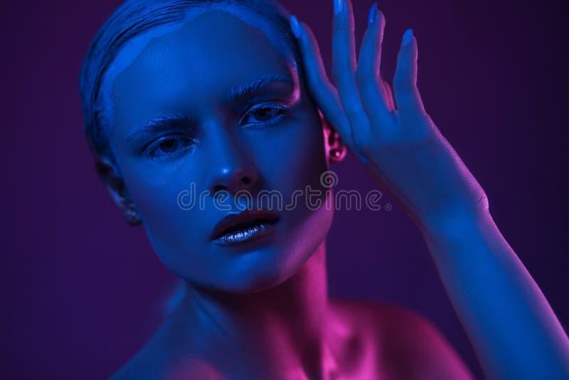 有凉快的年轻俏丽的妇女组成 在面孔的霓虹蓝色和紫色光 免版税库存照片