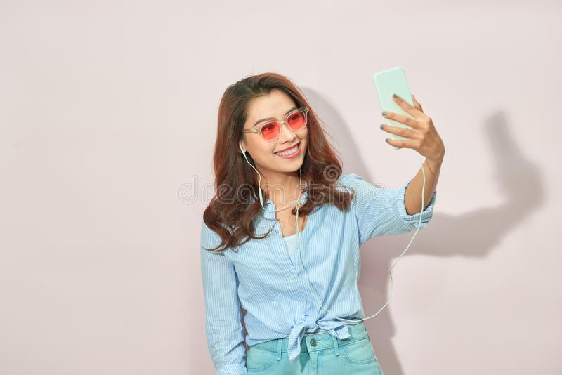 有凉快的快乐的女孩画象与恋人在手中射击在前面照相机的藏品智能手机的视频通话selfie被隔绝 库存图片