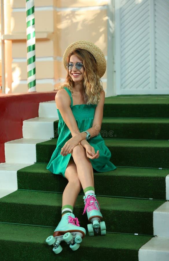 有减速火箭溜冰鞋坐的愉快的女孩 免版税图库摄影